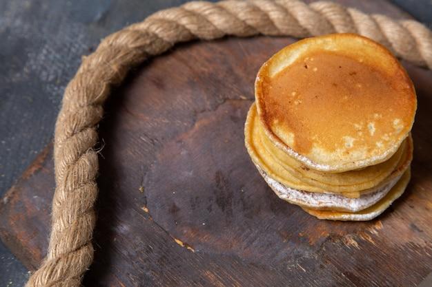 Muffin squisiti di vista frontale delizioso e cotto sullo zucchero dolce del pasto della colazione dell'alimento della scrivania di legno Foto Gratuite