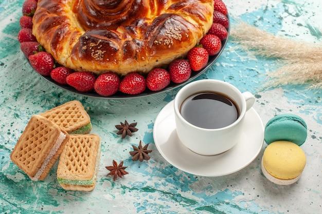 正面図新鮮な赤いイチゴのワッフルと青い表面にお茶のカップとおいしい甘いパイ 無料写真