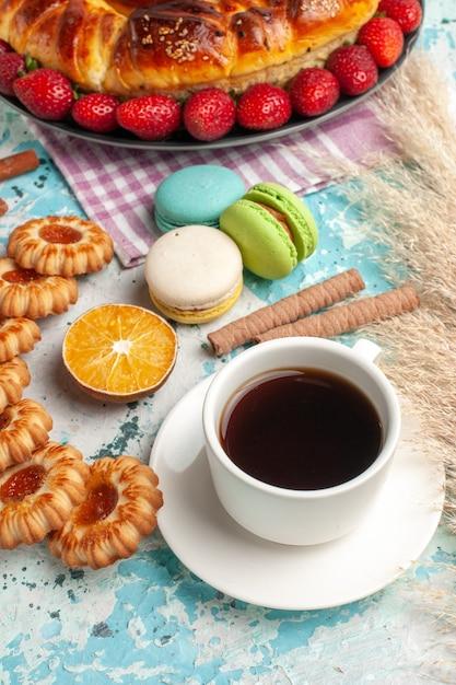 正面図青い表面に赤いイチゴのクッキーとお茶とおいしい甘いパイ 無料写真