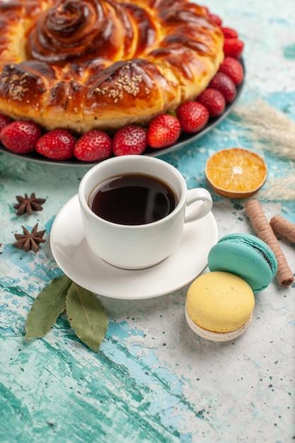 青い床にイチゴのマカロンとお茶の正面図おいしい甘いパイ 無料写真