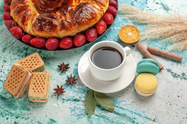 正面図イチゴワッフルと青い表面にお茶のカップとおいしい甘いパイ 無料写真