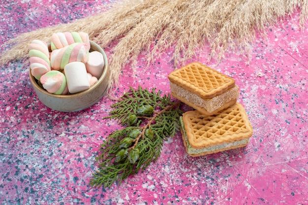 Vista frontale di deliziosi biscotti waffle con marshallow sulla scrivania rosa Foto Gratuite