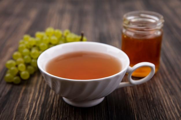 木製の背景の上の瓶に緑のブドウと蜂蜜とお茶の正面図 無料写真