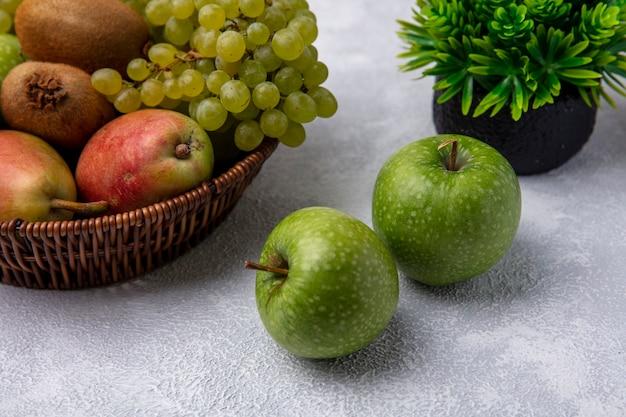 白い背景の上のバスケットに梨緑ブドウとキウイと正面図青リンゴ 無料写真
