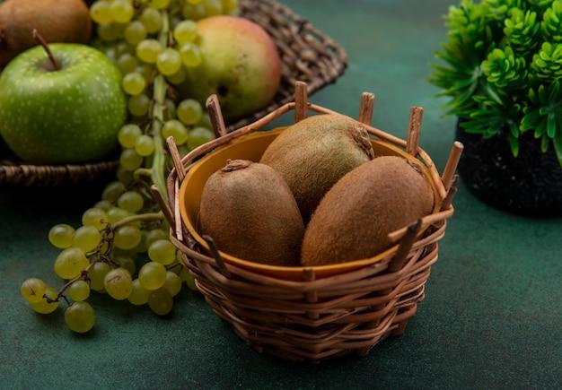 緑の背景に緑のブドウとリンゴとバスケットの正面図キウイ 無料写真