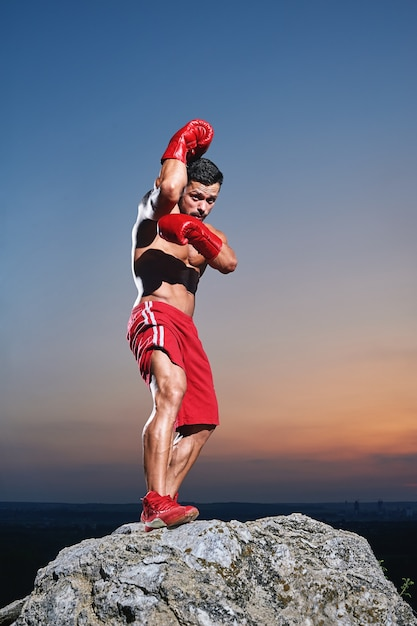 Frontview of muscular male boxer practising skills outdors Premium Photo