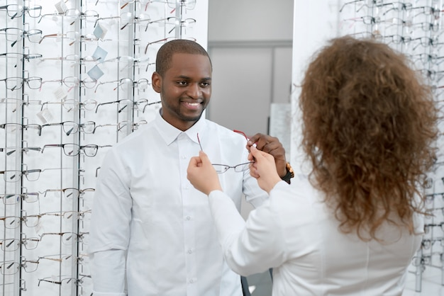 Frontview of smiling man trying on eyeglasses in optical shop. Premium Photo