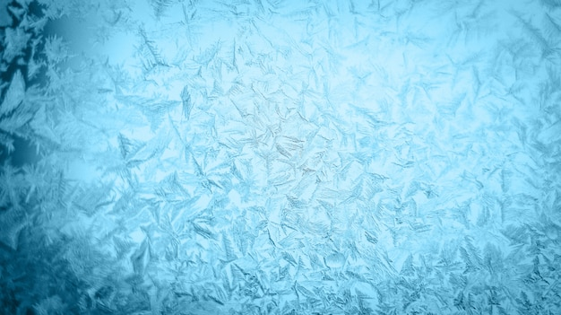 Frosty christmas pattern at a winter window glass Premium Photo