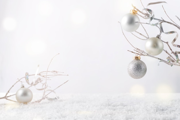 Frosty tree branch with snow and christmas decoration i on white . attach your product Premium Photo