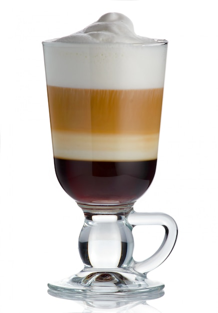 Frothy, layered cappuccino in a clear glass mug with cinnamon sprinkled Premium Photo