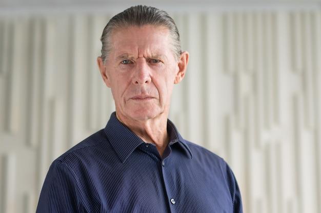 Frown serious angry senior man looking at camera Free Photo
