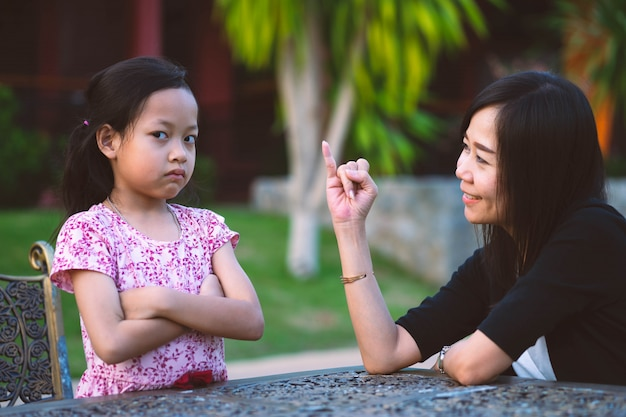 Frowned daughter are angry and mother apologized for showing her little finger. Premium Photo