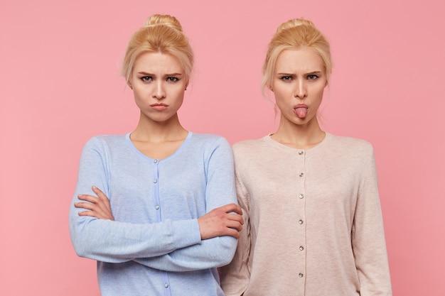 ピンクの背景の上に隔離されたカメラを見て、機嫌が悪い美しい若いブロンドの双子をしかめっ面。 無料写真