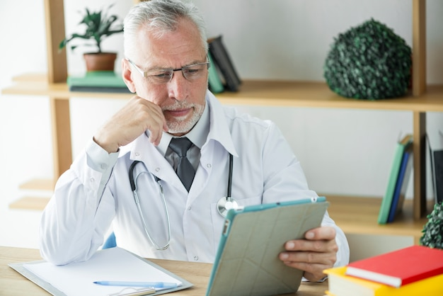 Frowning doctor using tablet in office Free Photo