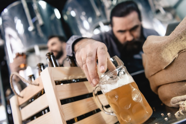 Frowning man inspecting beer in mug microbrewery. Premium Photo