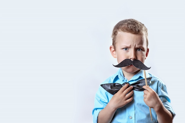 Frowning serious boy in a light shirt put a mustache on a stick and a bow tie on his face to make him look older. Premium Photo