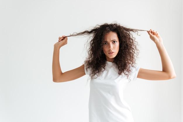 Хмурится неудовлетворенная женщина, касающаяся ее волос и смотрящая на камеру Бесплатные Фотографии