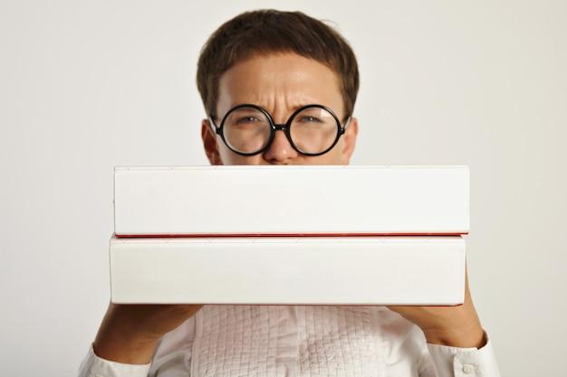 La giovane studentessa accigliata in occhiali rotondi tiene due grandi cartelle con un piano educativo per il nuovo anno all'università focus sulle cartelle Foto Gratuite