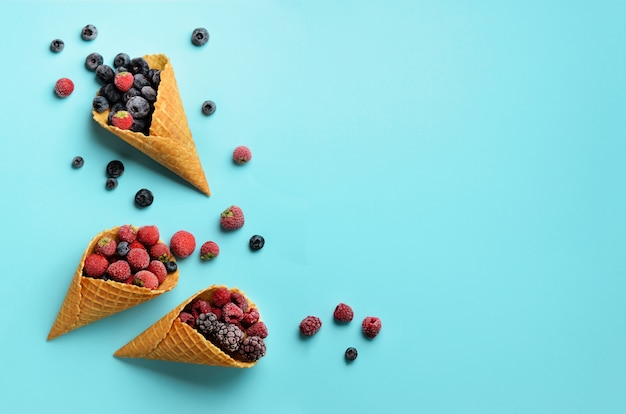 Frozen berries - strawberry, blueberry, blackberry, raspberry in waffle cones on blue background. Premium Photo