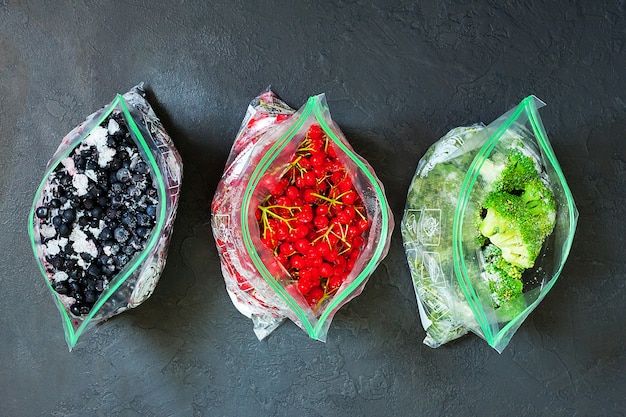 Frozen berries and vegetables in bags in packages on dark Premium Photo