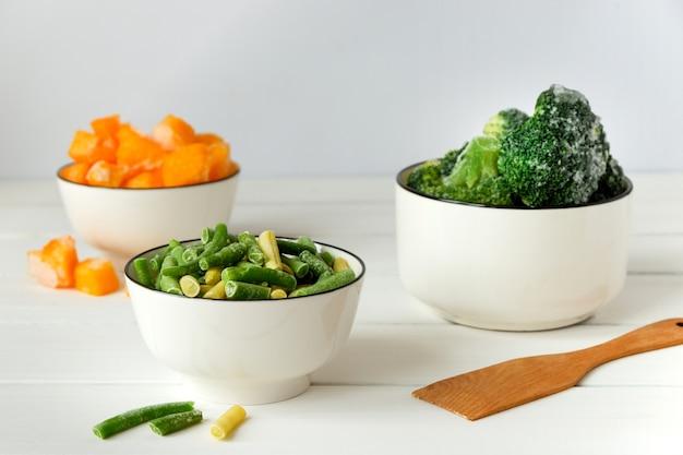 냉동 브로콜리, 프랑스 콩, 흰색 테이블에 흰 그릇에 호박 프리미엄 사진