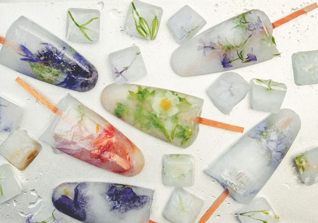 Frozen flowers in ice cubes and ice cream on a stick. selective focus. Premium Photo