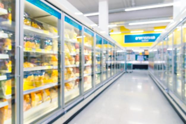 Frozen food freezers in the supermarket. defocused background. Premium Photo