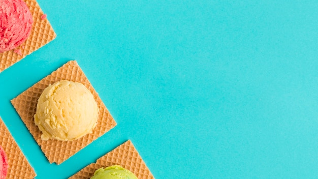 Frozen ice cream scoop on waffles on turquoise surface Free Photo