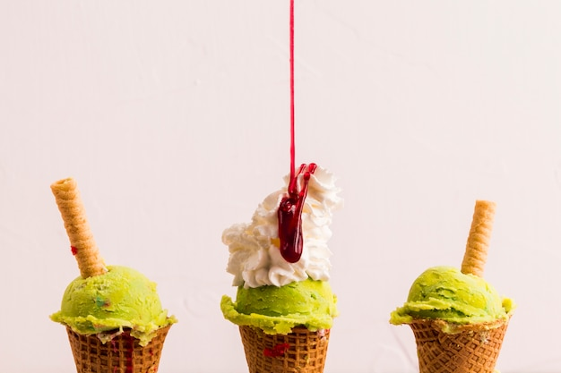 Frozen pistachio ice cream scoop in cones with waffle straw Free Photo
