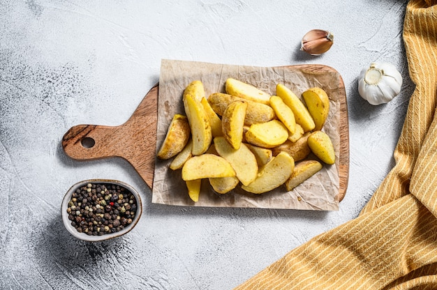 Frozen potato wedges on a cutting board. recipe for french fries. white background. top view Premium Photo