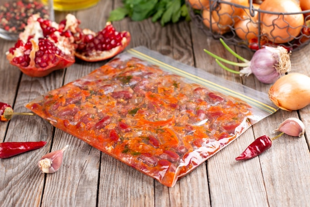 Frozen stewed red beans in tomato sauce in the bag on the wooden table Premium Photo