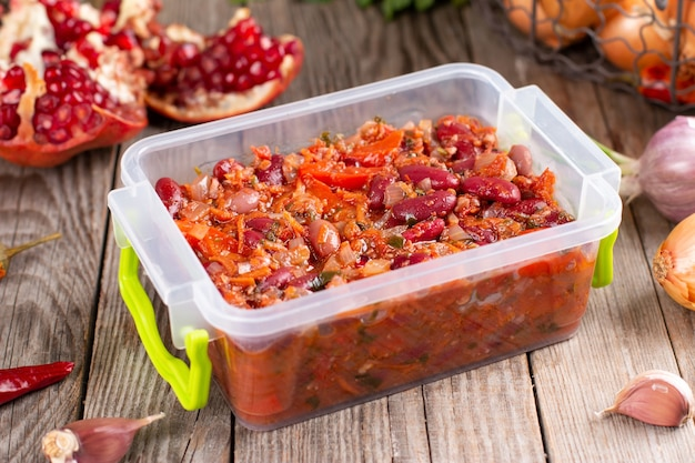 Frozen stewed red beans in tomato sauce in container on the wooden table Premium Photo