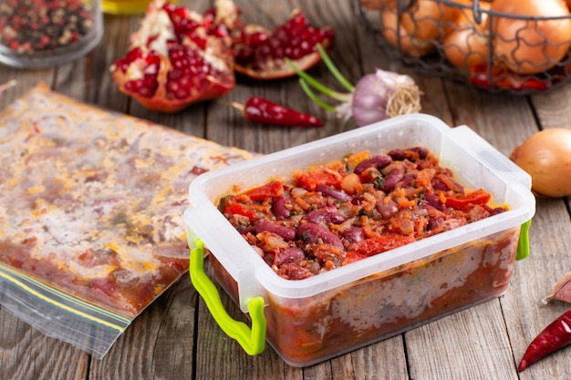 Frozen stewed red beans in tomato sauce on the wooden table Premium Photo