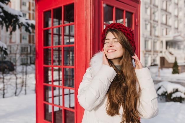 路上の赤い電話ボックスの近くの冬時間を楽しんでいる赤い帽子の長いブルネットの髪を持つ陽気な若い女性の凍結する晴れた雪の朝。目を閉じて笑って太陽の下で身も凍るように。 無料写真