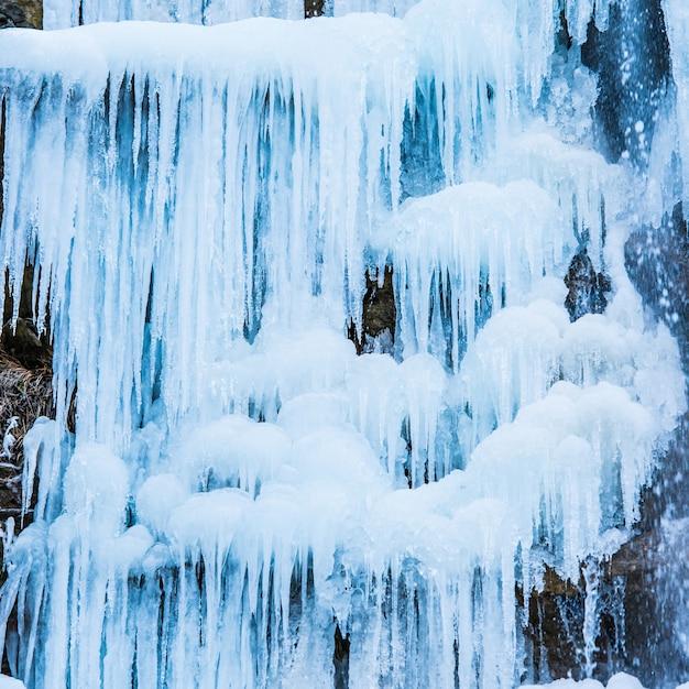 岩の上の青いつららの凍った滝 Premium写真