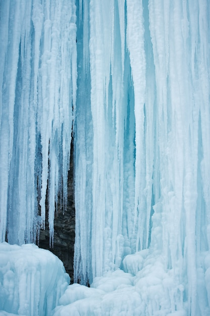 A frozen waterfall with ice in a blue and white color in winter Premium Photo