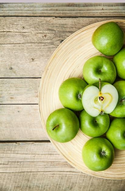 フルーツ。木製のテーブルの上のボウルにリンゴ Premium写真