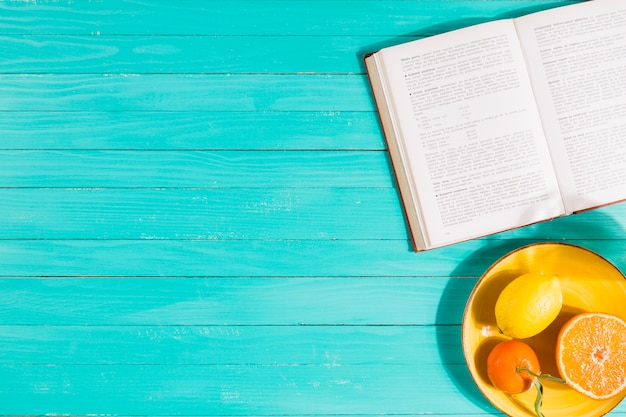 Fruit bowl and book on table Free Photo