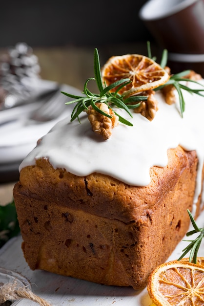 Fruit cake dusted with icing, nuts and dry orange close-up. christmas and winter holidays homemade cake Premium Photo