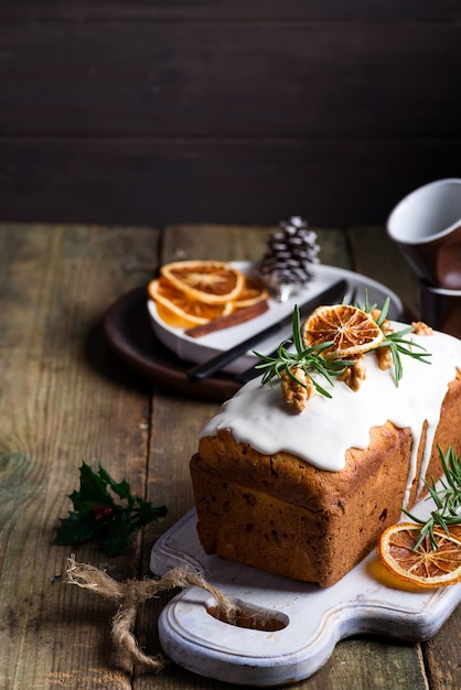 Fruit cake dusted with icing, nuts and dry orange on old wooden . christmas and winter holidays homemade cake Premium Photo
