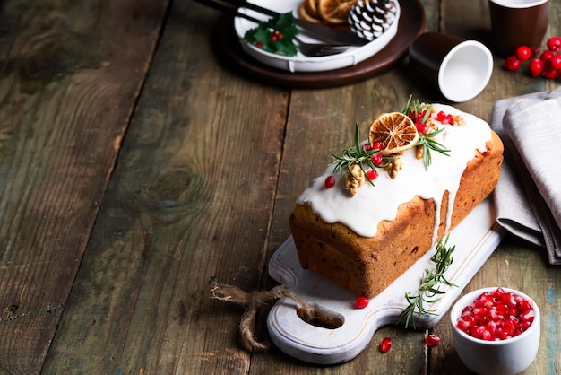 Fruit cake dusted with icing, nuts, kernels pomegranate and dry orange on old wooden . christmas and winter holidays homemade cake Premium Photo