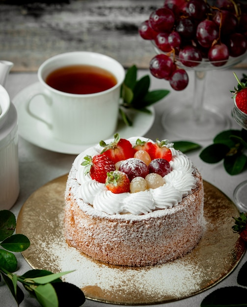 Fruit cake topped with strawberry white and red grape Free Photo