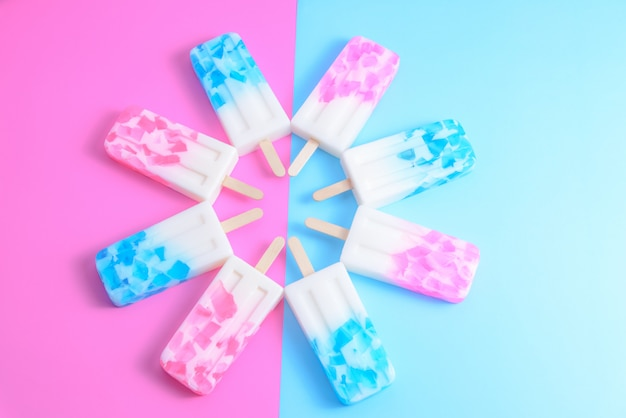 Fruit ice cream stick , popsicle , ice pop or freezer pop with copyspace on blue and pink pastel background or texture Premium Photo