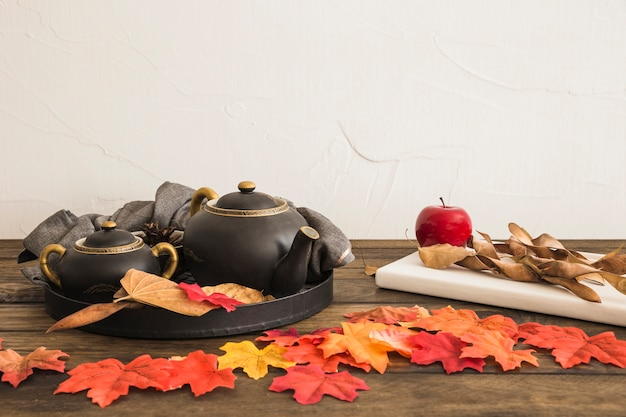 Fruit and notepad near leaves and tea set Free Photo