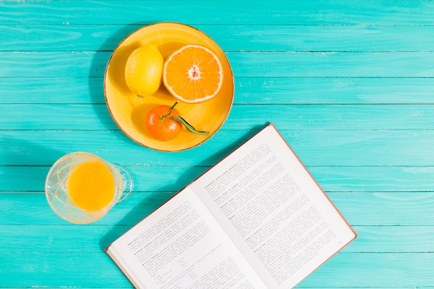 Fruit plate, juice glass and book on table Free Photo