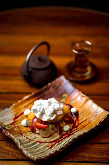 Fruit plate topped with cream and sugar powder Free Photo