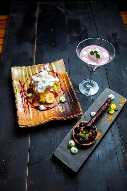 Fruit plate with cream, chocolate tartaleta and blueberry pouding Free Photo