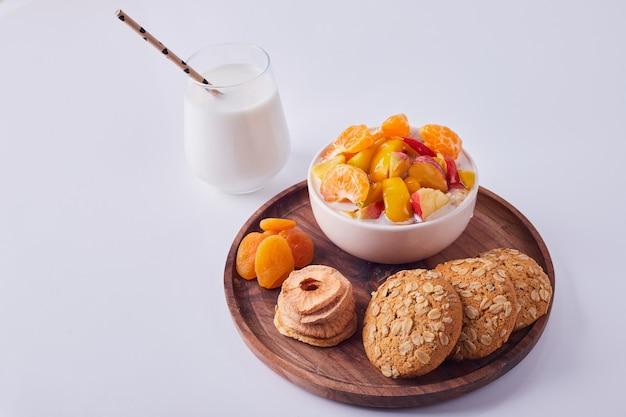 脇のミルクのガラスと木の板にオートミールクッキーとクリームのフルーツサラダ、上面図。 無料写真