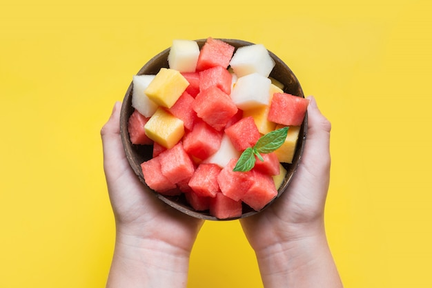 Fruit salad of watermelon, melon and peach in coconut bowl in hands of child Premium Photo