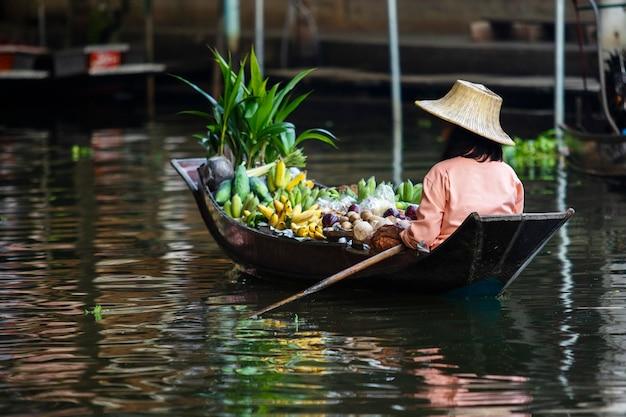 Fruit seller sailing boat in dumneon saduak floating market ratchaburi thailand Premium Photo